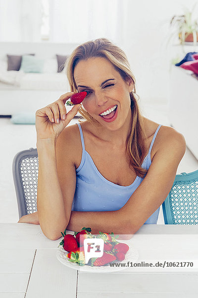 Porträt einer blonden Frau  die am Tisch sitzt und sich mit Erdbeeren amüsiert.