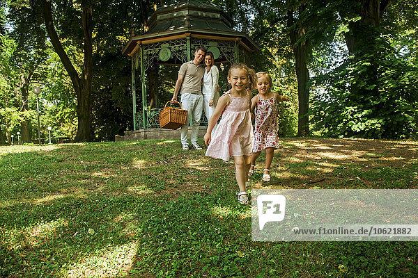 Glückliche Familie im Park  Eltern mit Picknickkorb