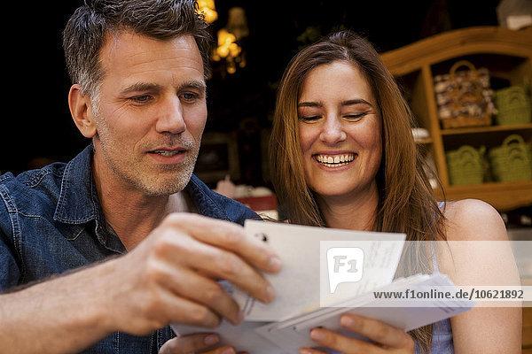 Glückliches Paar beim Betrachten von Postkarten