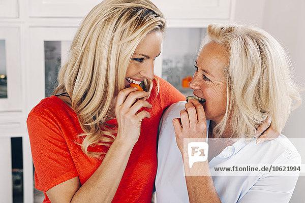 Lächelnde erwachsene Tochter mit ihrer Mutter beim Gemüseessen