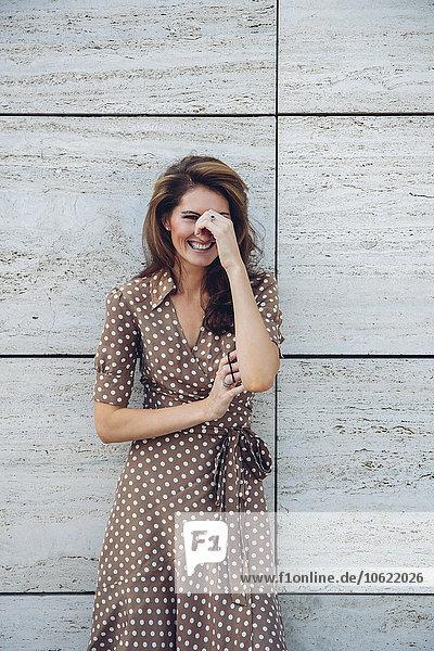 Porträt der lachenden brünetten Frau im Freien