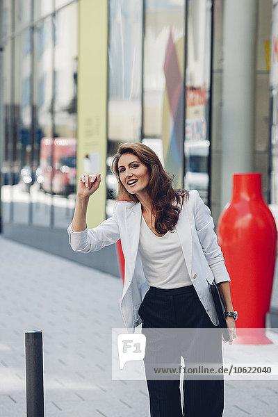 Lächelnde Geschäftsfrau auf dem Bürgersteig  die ein Taxi ruft.