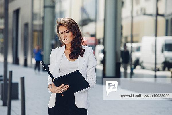 Geschäftsfrau im Freien beim Betrachten der Akte