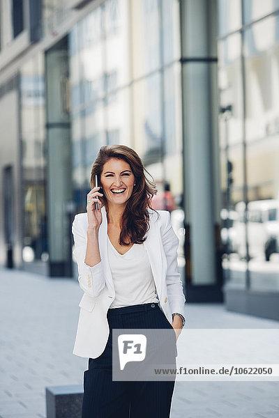 Glückliche Geschäftsfrau im Freien am Handy