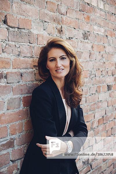 Porträt einer lächelnden Geschäftsfrau  die sich an die Wand lehnt.