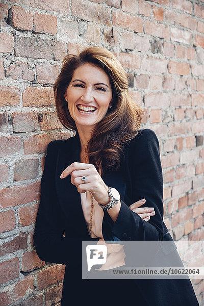 Porträt einer glücklichen Geschäftsfrau  die sich an die Wand lehnt.