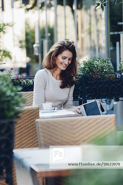 Lächelnde Frau in der Einkaufstasche im Outdoor-Café