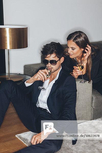 Stilvolles junges Paar mit Gläsern Champagner auf dem Sofa