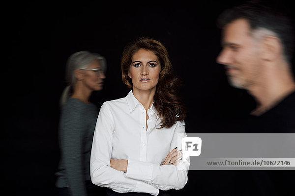 Porträt einer Geschäftsfrau mit gekreuzten Armen vor schwarzem Hintergrund