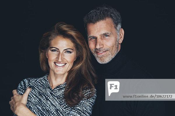 Porträt des lächelnden Paares vor schwarzem Hintergrund