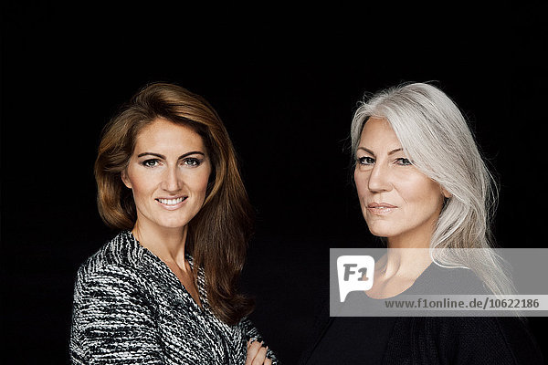 Portrait of two women in front of black background