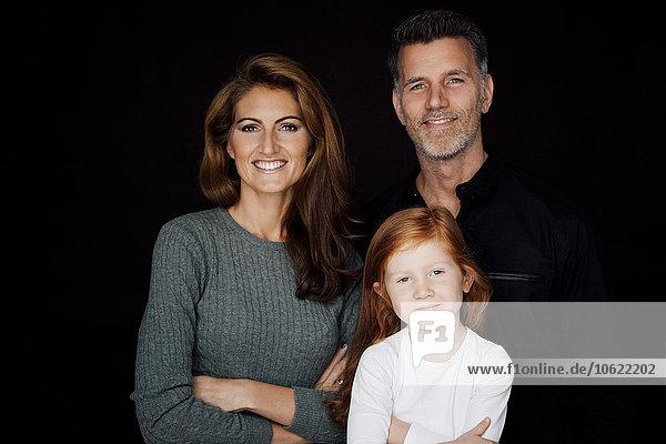 Porträt eines lächelnden Paares mit kleiner Tochter vor schwarzem Hintergrund
