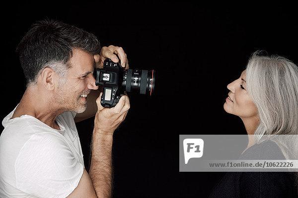 Mann fotografiert Frau vor schwarzem Hintergrund