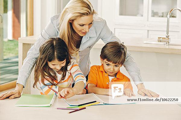 Mutter betrachtet ihre Kinder mit Malbuch