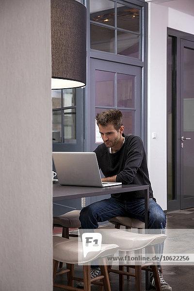 Junger Mann am Tisch sitzend mit Laptop