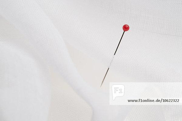 Rote Nadel in weißem Tuch