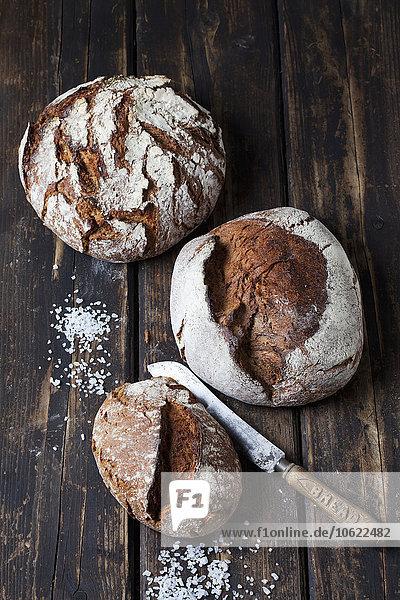 Drei knusprige Brote  Brotmesser und gestreute Salzkörner auf dunklem Holz