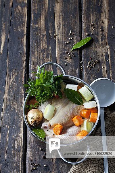 Kochtopf mit rohem Hühnerfleisch  Zwiebeln  Kräutern und Gemüse