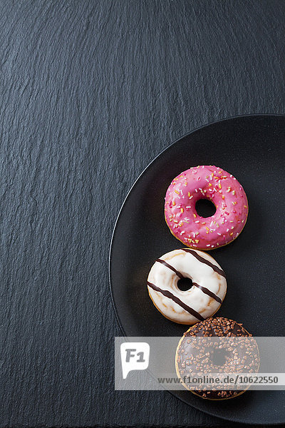 Drei Doughnuts mit verschiedenen Glasuren auf Schwarzblech und Schiefer