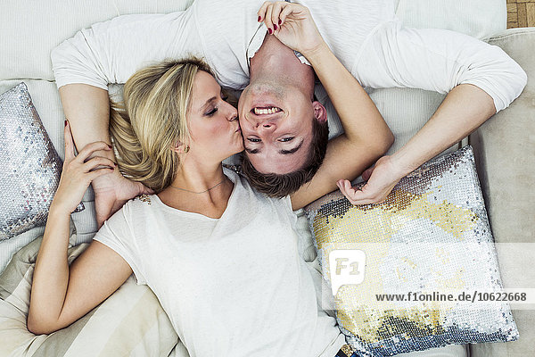 Junges Paar im Bett liegend  küssend