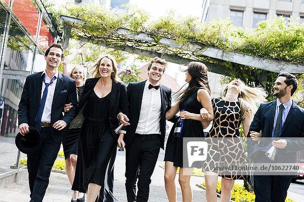 Gruppe von gut gekleideten  fröhlichen Freunden  die im Freien spazieren gehen.