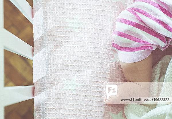 Fuß des Mädchens im Kinderbettchen Fuß des Mädchens im Kinderbettchen