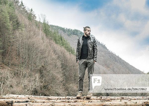 Bulgarien  Rhodopen  junger Mann auf Baumstämmen stehend