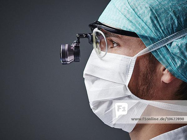 Junger Arzt mit Maske und Lupenbrille