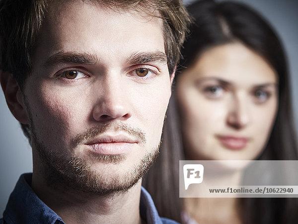 Porträt eines ernsthaften jungen Mannes mit Freundin im Hintergrund