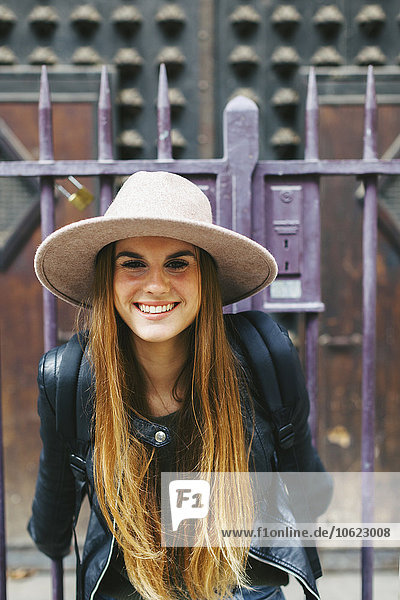 Spanien  Barcelona  lächelnde junge Frau vor dem Eingangsportal