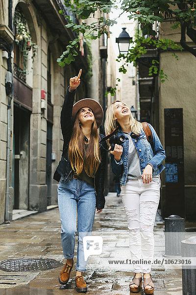 Spanien  Barcelona  zwei junge Frauen  die in der Stadt spazieren gehen und nach oben schauen.