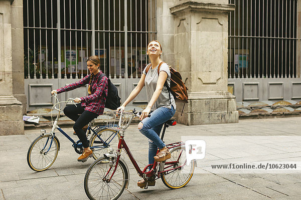 Spain  Barcelona  two young women riding bicycle in the city