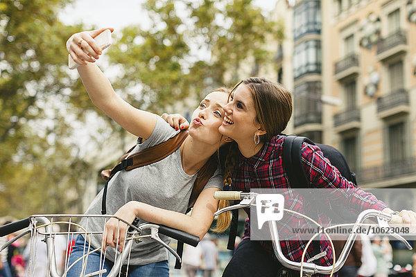 Spanien,  Barcelona,  zwei junge Frauen auf Fahrrädern mit einem Selfie