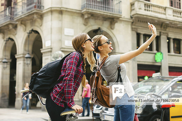 Spain  Barcelona  two playful young women taking a selfie
