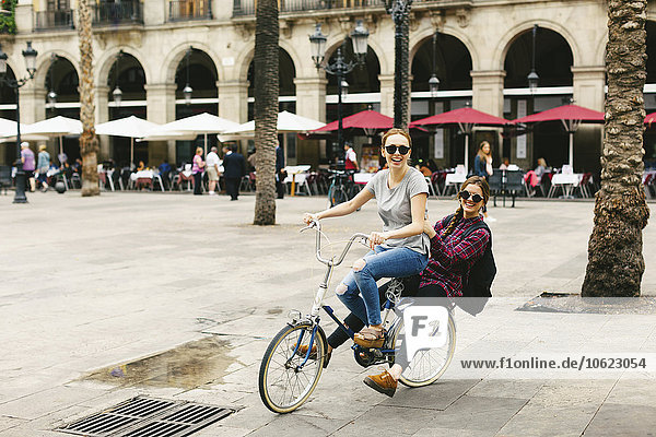 Spain  Barcelona  two happy young women sharing bicycle in the city