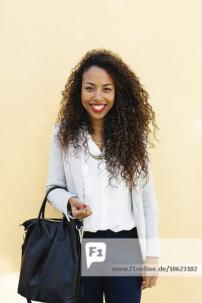 Portrait of smiling young businesswoman with leather bag in front of a yellow wall