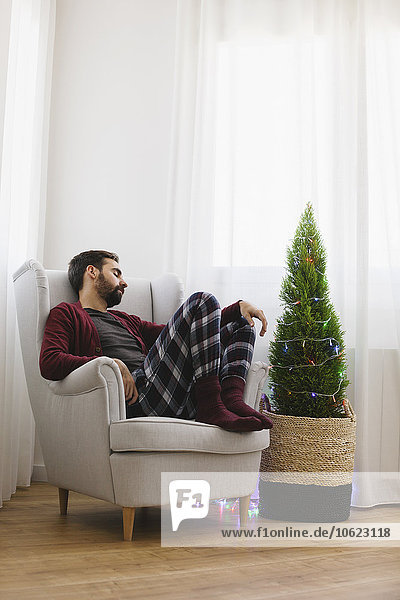 Mann schlafend auf Sessel zu Hause zur Weihnachtszeit