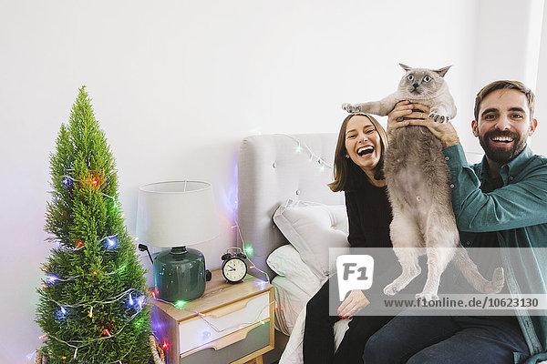 Lachendes Paar mit seiner Katze zu Hause