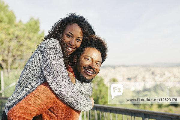 Spanien  Barcelona  Porträt eines glücklichen jungen Mannes  der seine Freundin huckepack fährt.