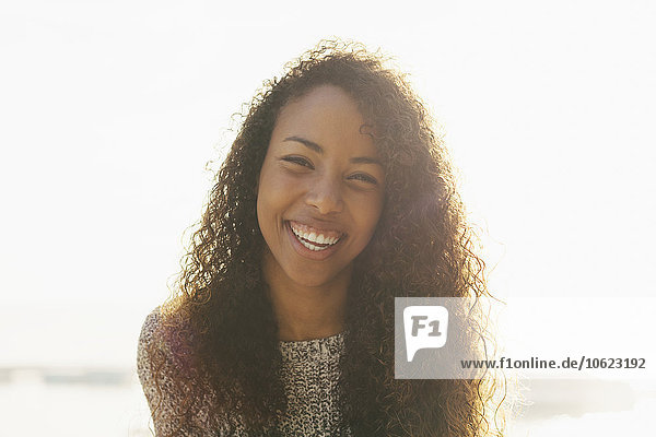 Portrait of smiling young woman with curly brown hair at backlight