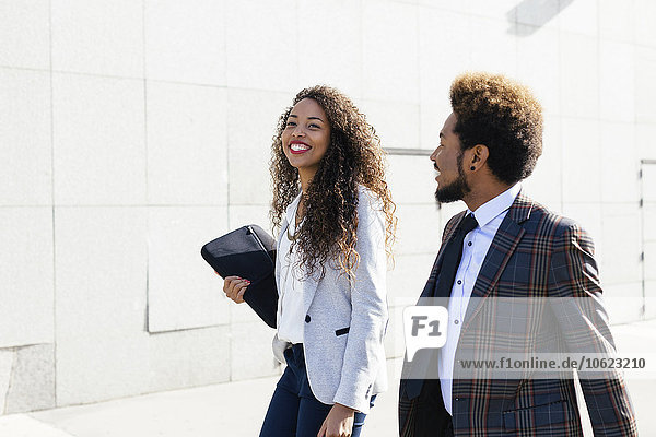 Two smiling young business people outdoors