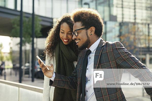 Zwei lächelnde junge Geschäftsleute im Freien  die auf das Smartphone schauen.