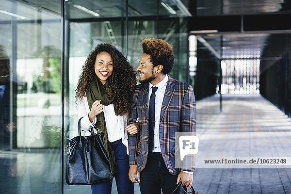 Zwei lächelnde junge Geschäftsleute im Freien