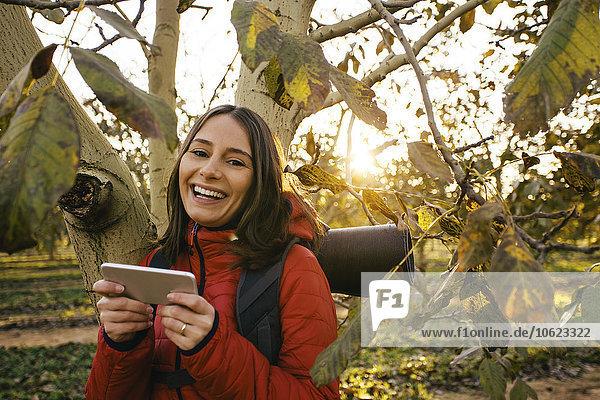 Spanien  Katalonien  Girona  Portrait einer glücklichen Wanderin mit Handy am Baum