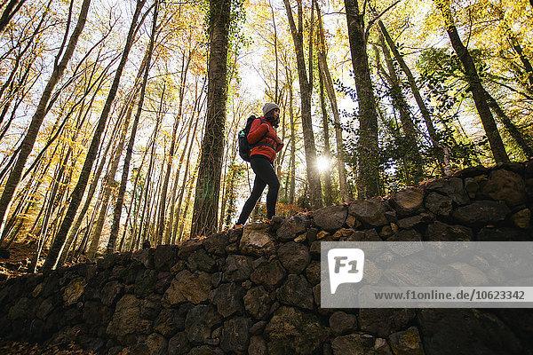 Spanien  Katalonien  Girona  Wanderin auf Steinmauer im Wald