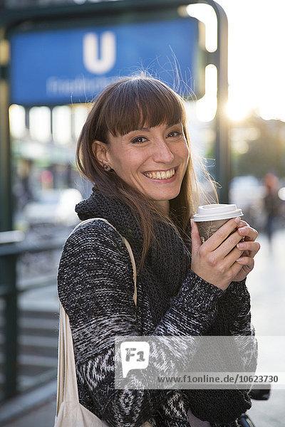 Deutschland  Berlin  Portrait einer glücklichen jungen Frau mit Kaffee zum Mitnehmen