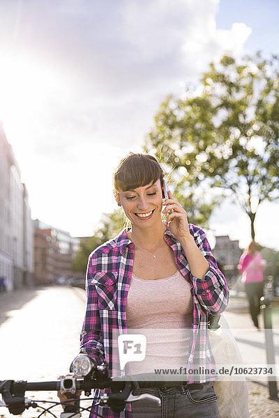 Deutschland  Berlin  Portrait einer lächelnden jungen Frau mit Fahrradtelefonie mit Smartphone