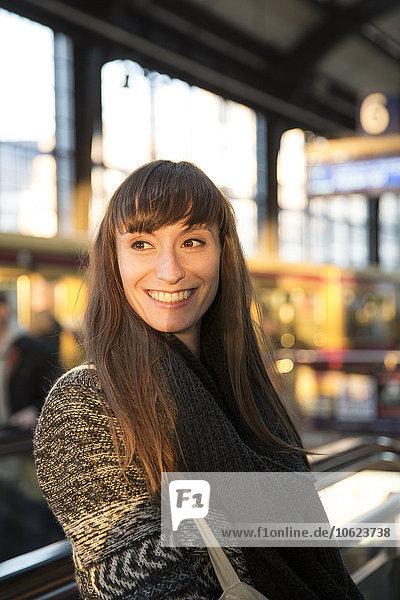Germany  Berlin  smiling young woman waiting at platform
