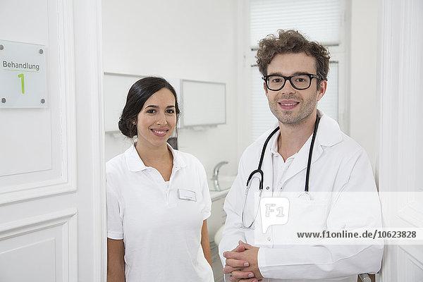 Porträt des lächelnden Arztes und Arzthelfers in der Praxis