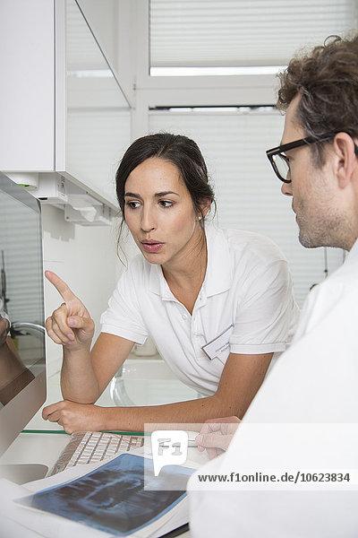 Zwei Ärzte am Computerbildschirm diskutieren über